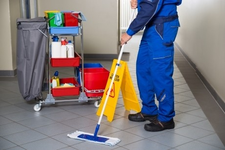 janitor mopping tiled floor in an office building