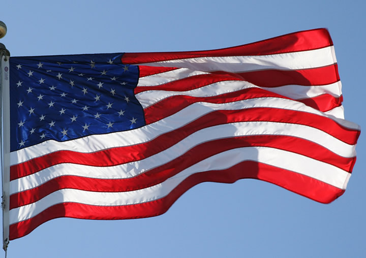 American flag flying over a blue sky with no clouds
