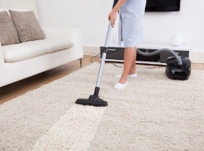 maid vacuuming a rug carpet